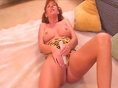 Ugly redhead Christi Lake is busy with stimulating her mature pussy