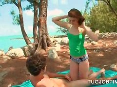 Redhead teeny tugging her BFs shaft at the beach