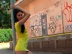 Appetizing and bright brunette in yellow dress gets naked in the streets