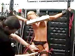 Blonde gets tits nailed to a board