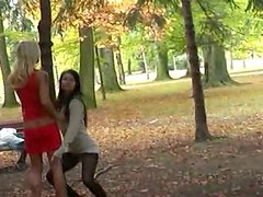 Sassy girls are posing on cam standing along the tree in a public park