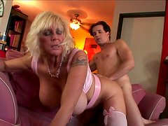 Horn-mad busty crone rides a dick passionately on the couch for orgasm