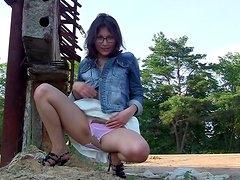 Brunette in glasses makes an upskirt outdoors