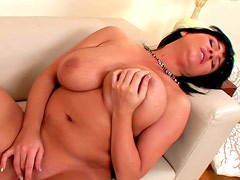 Brunette with big tits Kora is playing with her shaved pussy