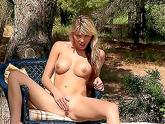Salacious blonde chick masturbating with a dildo in the garden