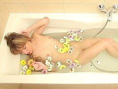 Kinky romantic light haired chick takes a bath with flower petals