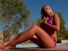 Sultry tanned blonde Cara takes a sun bath over the poolside