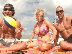 Busty slutty Ingrid Swenson seduces two men on the beach and wins the cocks