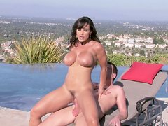 Buxom brunette Lisa Ann is riding a stiff dick right outdoors