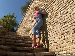 Pretty Dorina fingers her wet pussy on the stairs in the street