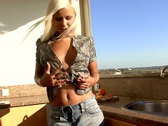 Blonde girl toys her pussy with golden dildo in a kitchen