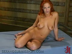 Redhead milf tied up and whipped on the floor.