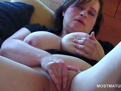 Close-up with busty mature rubbing her shaved pussy
