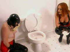 Luscious chic with head covered with mask washes toilet bowl with brush in her mouth