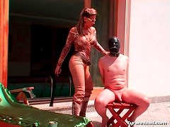 Mistress in boots steps on his cock outdoors
