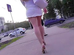 Hot babe in short white dress is walking on the street
