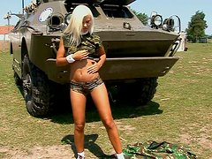 Sweet teen in military costume is posing on the tank