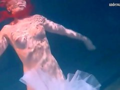 Cute ballerina swims in her shoes and tutu