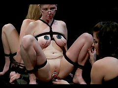 Brunette dominatrix playing with two busty submissive blondes
