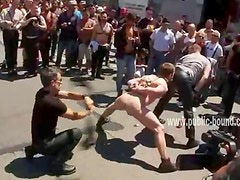 Gay slave is flogged has his mouth covered and his nipples pinched in a public street