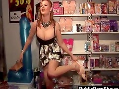 Busty redhead having fun in sex shop