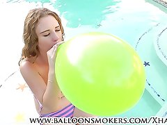 Teens blows to pop balloons outside by pool