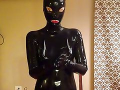 latex catsuit and hood and putting on rubber gloves