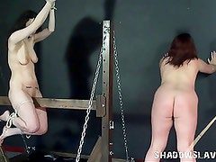 Wooden bondage and palm spanking of two caned lesbians