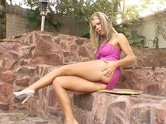 Slim Trisha plays with her shaved pussy in a backyard