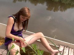 Brunette sits on a boat and fingers her smooth twat