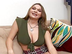 Busty blonde masturbates with a dildo on the couch