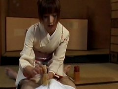 Asian brunette is giving an awesome handjob