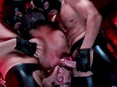 Suspended brunette gives submissive blowjob to a duo of dudes