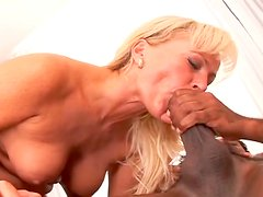 Sexy MILF riding a black cock in her bedroom