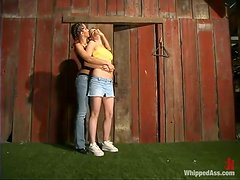 Blonde and brunette girls toy each other in a barn