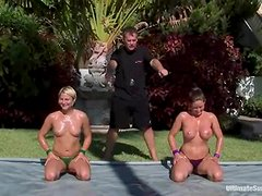 Oiled up chicks with big boobs wrestle outdoors