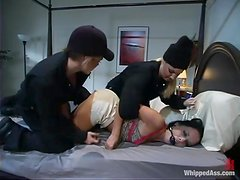 A brunette gets whipped and fucked by two dominant blondes