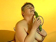Lewd granny Julie moans loudly while fucking her vag with a cucumber