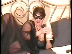 Mature lady in mask is tickling her twat
