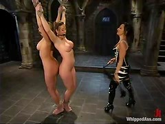 Two submissive girls in latex dresses get punished by a mistress
