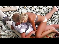 Voyeur on public beach. The suntanned girl rides on the guy