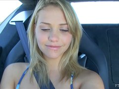 A seductive blonde shows her nice boobs in a car