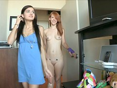 A brunette and a redhead girls play lesbian games in a bedroom