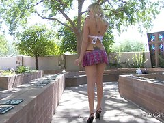 A cute blonde in a miniskirt pushes a lollipop in her pussy