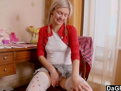 A cute blonde with pigtails toys her tight ass and pussy in a bedroom