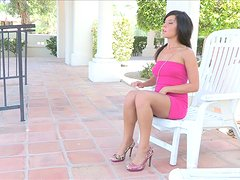 A sexy girl in a pink dress shows her big boobs on a balcony
