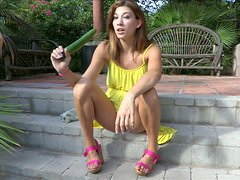 A slim girl in a yellow dress inserts a cucumber in her pussy