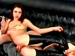Dirty brunette is smoking on the black sofa