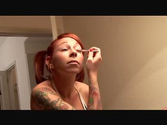 Heavily tattooed redhead with pigtails puts on makeup