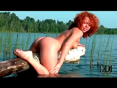Curly haired redhead teases by the lake